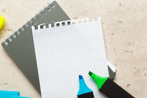 Blue and green highlighters on blank notepad paper sheet flat lay on a desk