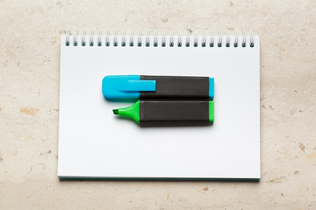 Blue and green highlighters on blank notepad paper sheet flat lay on desk