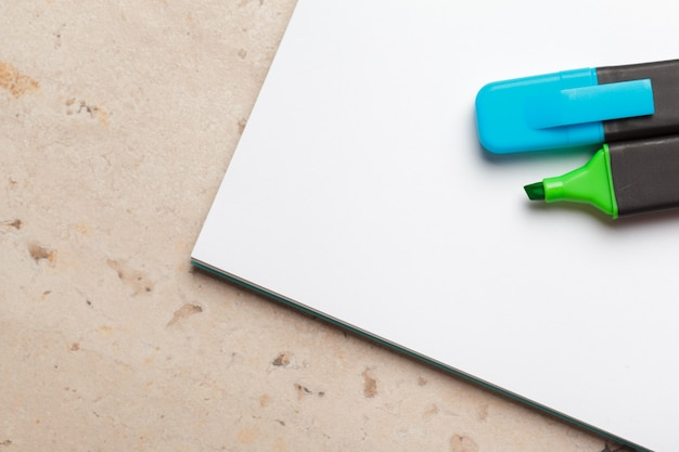 Blue and green highlighters on blank notepad paper sheet