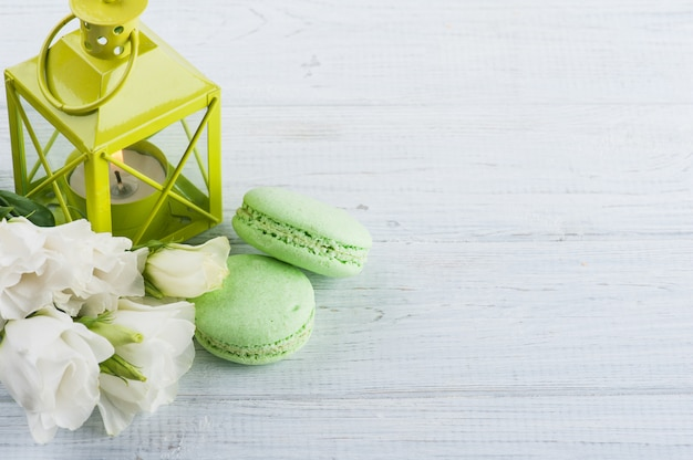 Blue green macaroons and lit candle in lantern