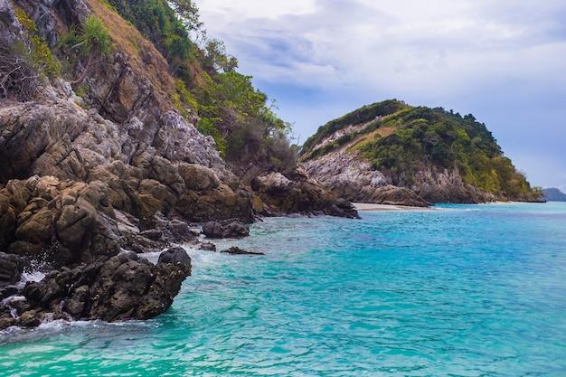 雲の日でいっぱいの岩山と青緑色の海。シービューと自然の背景。