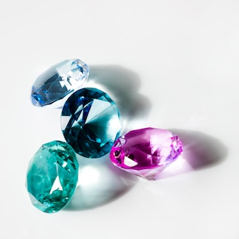 Blue; green and pink shiny diamonds with shadow on white background