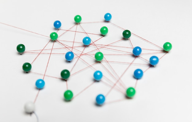 Blue and green pushpins with thread for route map