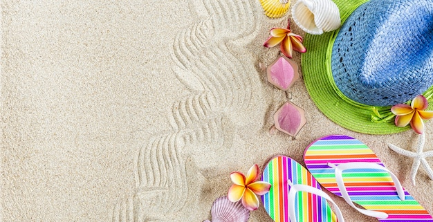Blue and green straw hat and colorful flip flops in the sand with shells and frangipani flowers. summertime on beach concept, copy space
