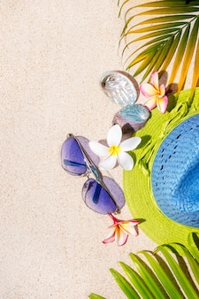 Blue and green straw hat with sunglasses, sea shells and frangipani flowers with green palm leafs on sand.