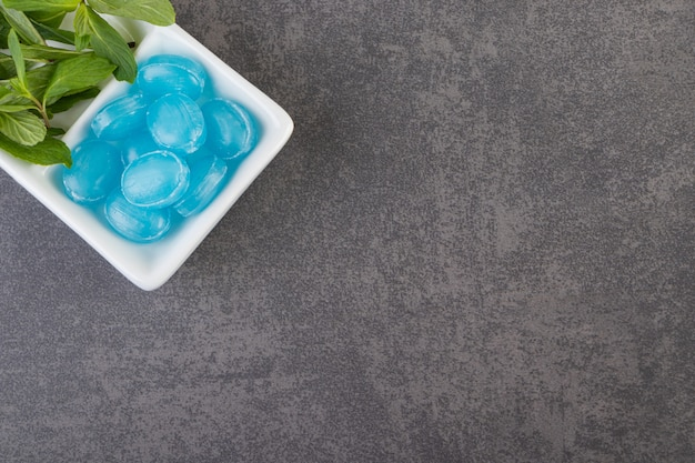 Blue gum with mint leaves on grey background.