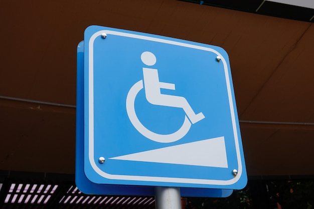 Blue handicap at parking car sign outdoors for disabled and wheelchair.