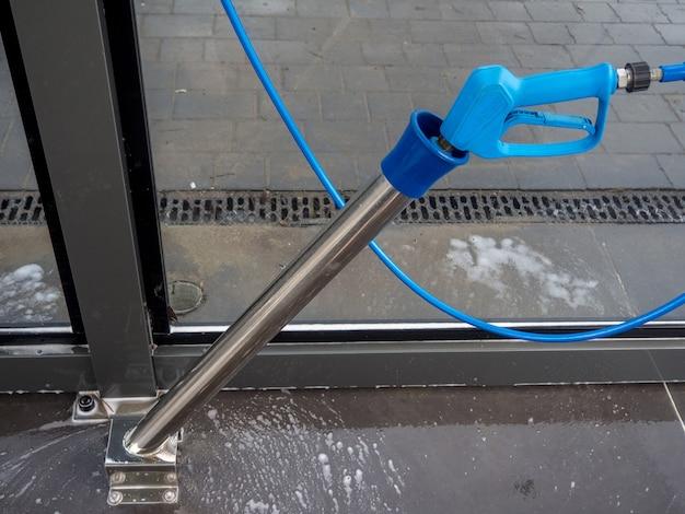 금속 실린더에 삽입된 긴 노즐이 있는 세차 고압 물총의 파란색 손잡이. 셀프 서비스 세차장에서 거품이 있는 권총의 자른 사진.