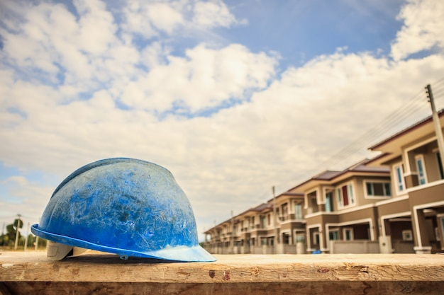 Blue hard hat on house building construction site