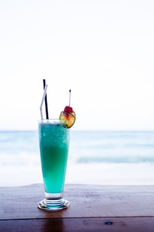Blue hawaii cocktail on table beach background.
