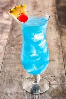 Синий гавайский коктейль на деревянном столе