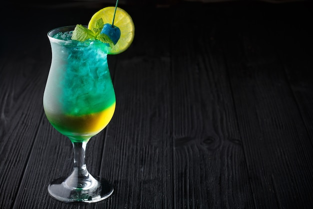 Blue hawaiian cocktail with mint on black background