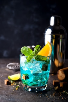 Blue hawaiian lagoon cocktail on a dark concrete background