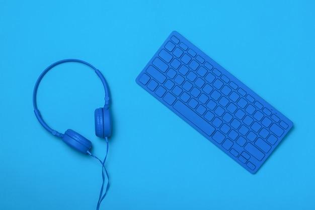 블루 헤드폰과 파란색 표면에 파란색 키보드. 사무실 액세서리의 흑백 이미지입니다.