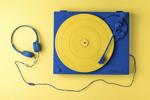 파란색 헤드폰 및 노란색 배경에 노란색 파란색 비닐 레코드 플레이어. 복고풍 음악 장비.