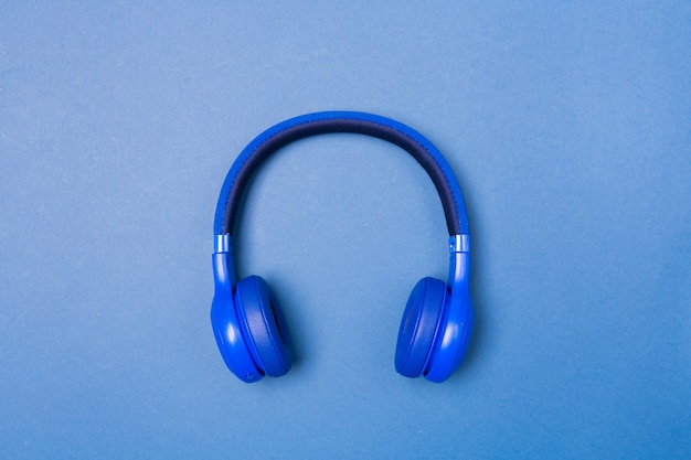 Blue headphones on blue background, top view. copy space. space for text.