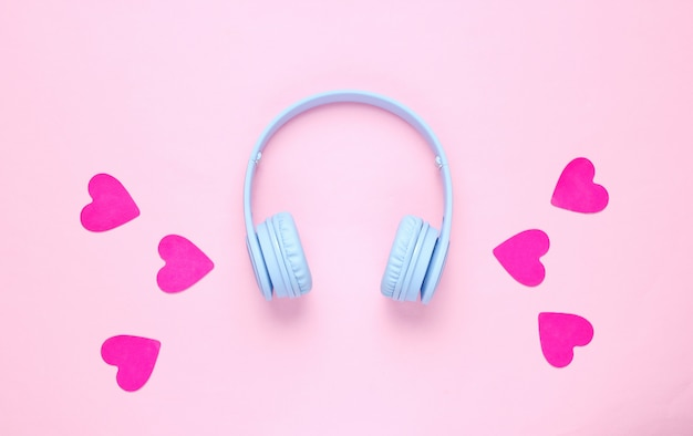 Blue headphones and hearts on pink background