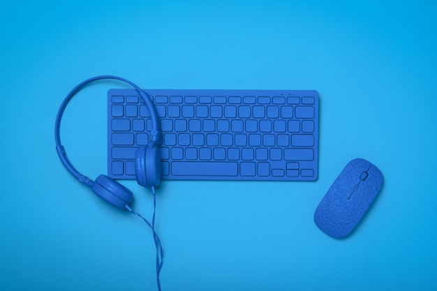 블루 키보드에 블루 헤드폰과 블루 표면에 블루 마우스. 사무실 액세서리의 흑백 이미지입니다.