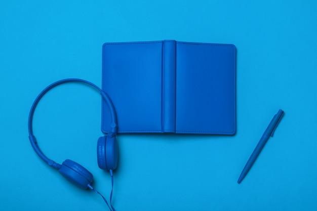 블루 헤드폰, 펜 및 메모장 파란색 표면에. 사무실 액세서리의 흑백 이미지입니다.