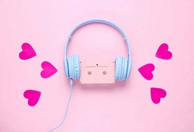 Blue headphones with audio cassette and hearts on pink background