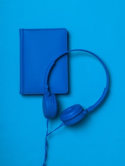Blue headphones with a blue leather notebook on a blue surface. monochrome image of office accessories.