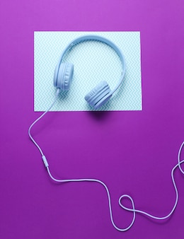 Blue headphones with cable on blue purple creative background