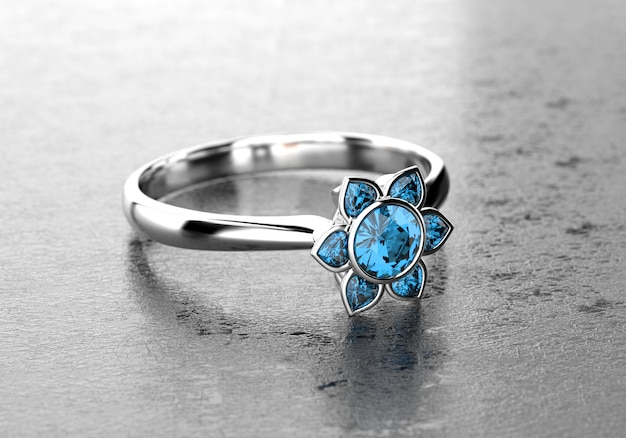 Blue heart and round shape diamond ring placed on glossy background