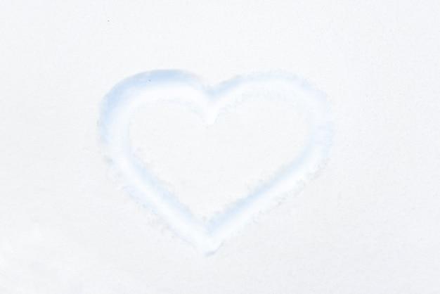 愛のバレンタインの背景として白い雪に描く青いハートの形