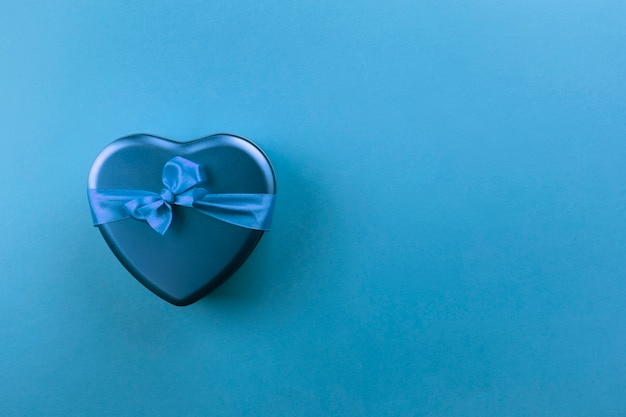 Blue heart-shaped box with ribbon on blue background. top view, copy space