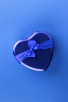 Blue heart-shaped box with ribbon on blue background