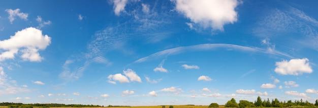 Голубое небо высоты над лугом с некоторыми облаками. образ сшивают семь кадров.