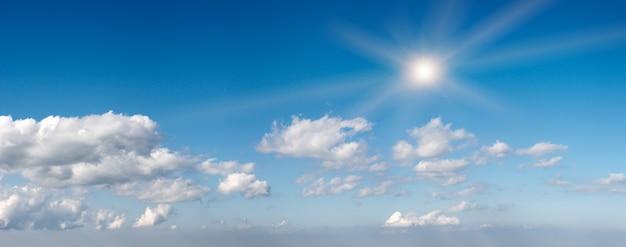 太陽といくつかの雲と山の上の青い高さの空。 6ショットステッチ画像。