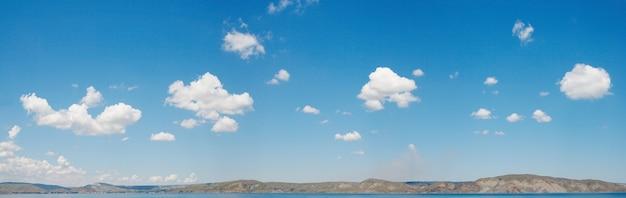 Голубое небо высоты над поверхностью моря с некоторыми облаками. изображение сшивается тремя кадрами.