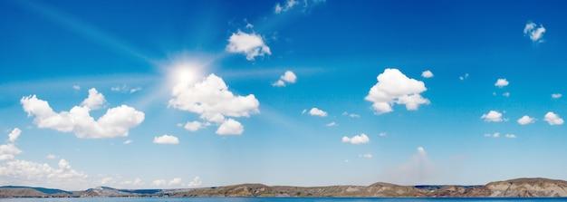 太陽といくつかの雲と海面上の青い高さの空。 3ショットステッチ画像。