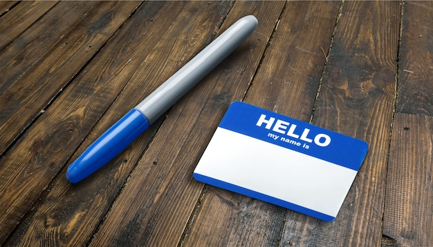 Blue hello my name is tag and pen on table with copy space,
