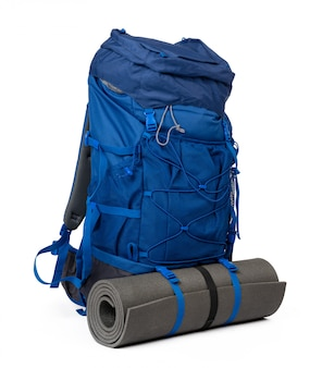 Blue hiking backpack with fitness mat isolated on white