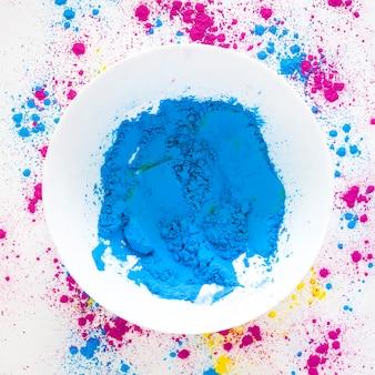 Синий холи цветной порошок в белой миске на белом фоне