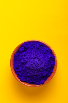 Blue holi powder in bowl isolated on yellow surface