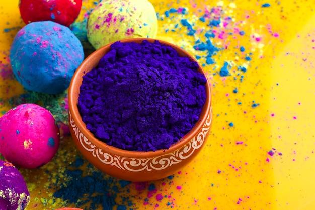그릇과 노란색 표면에 고립 된 여러 가지 빛깔의 공에 블루 holi 분말