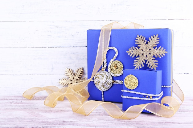 Синие праздничные подарочные коробки и лента на столе на деревянной стене