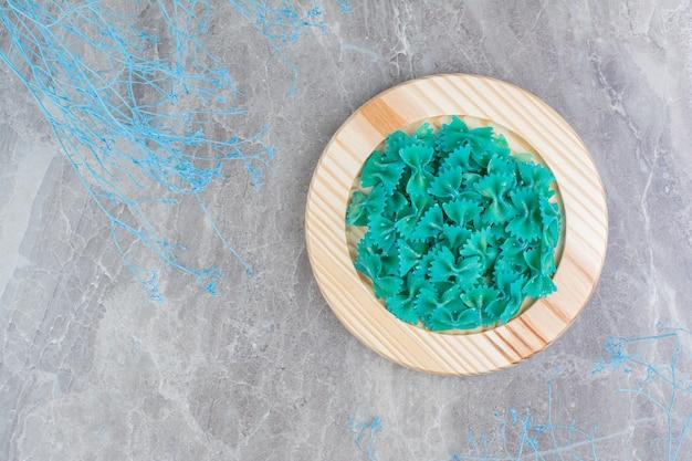 丸い木製の大皿に青い自家製パスタ