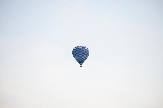 空を飛んでいる青い熱気球