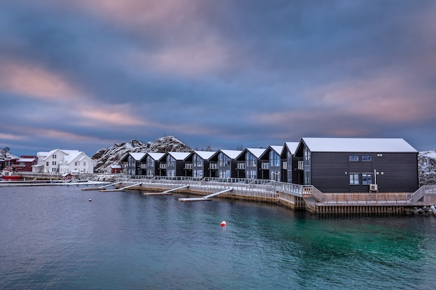 Blue hour after sunset time in winter season, village is covered with snow. the famous tourist attraction hamn village, senja islands, norway