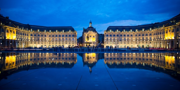 Blue hour buildings reflected in the water mirror across from place de la bourse in french city of bordeaux