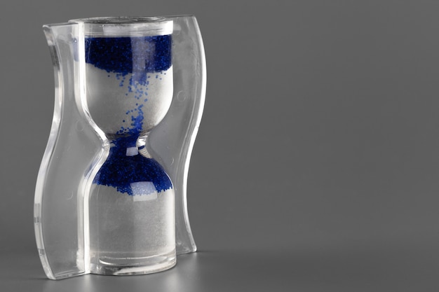회색 표면에 파란색 모래 시계를 닫습니다.