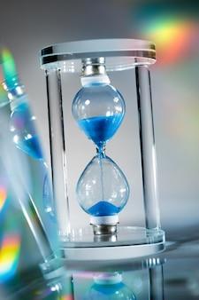 灰色の表面の青い砂時計のクローズアップ