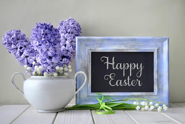 Синие гиацинты и цветы ландыша вокруг доски в соответствующей рамке