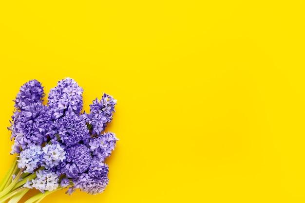 黄色の背景に青いヒヤシンスの花束母の日バレンタインデー誕生日のお祝いのコンセプト