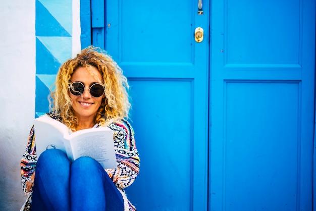 本を読んで楽しんでいるbeuaitufl幸せな陽気な大人の女性の青い画像の肖像画は、背景に家とドアを置いて床に座ります-アウトドアレジャー活動で勉強して読んでいる人々