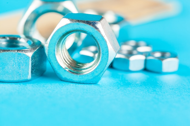 Blue industry or construction with various nuts on  blue surface